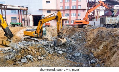Powerful excavators dismantle concrete. Construction site. Dismantling of an industrial building. The destruction of reinforced concrete.