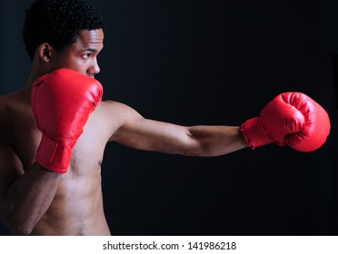 Powerful fighter portrait-isolated on black background. Young african ethnicity Boxer fighter isolated in black