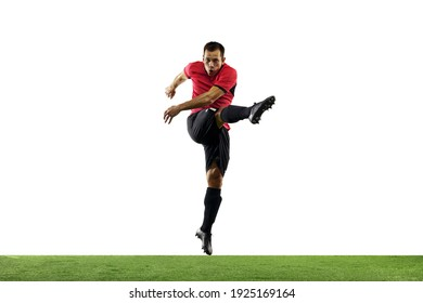 Powerful, flying above the field. Young football, soccer player in action, motion isolated on white background with green grass. Concept of sport, movement, energy and dynamic, healthy lifestyle.
