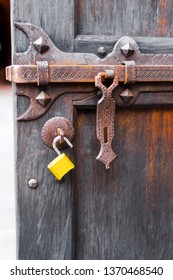 Powerful Forged bolt carved with ornaments and parts for closure on an old wooden door with rust on the deadbolt and modern open yellow padlock, as a meeting of old and new eras.