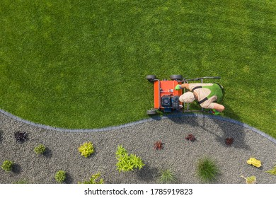 Powerful Gasoline Lawn Aerator Job For Controlling Lawn Thatch, And Reducing Soil Compaction. Backyard Grass Field Maintenance. Caucasian Gardener in His 40s. Aerial View.