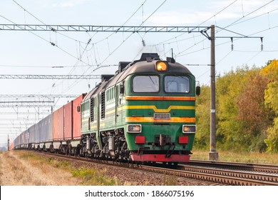 A powerful green diesel locomotive 2M62 pulls a freight train along the tracks of a railway station. Autumn photo.