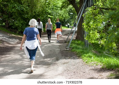 Powerful happy elderly people are walking, running early in the park Stockholm, Sweden