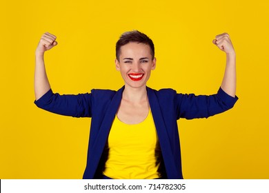 I am powerful and happy. Portrait of a happy elegant business woman showing power her biceps on yellow background. Girl short hair red lips blue suit yellow shirt