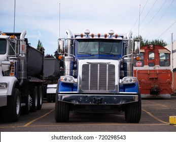 Powerful heavy-duty semi trucks washed after work day on the transportation of construction loads dump trucks are parked in an industrial production park at the end of the working day
