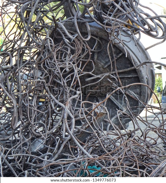 A powerful industrial magnet picks up scrap metal from a demolition project