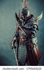 Powerful knight in the armor with the sword. Dark background.
