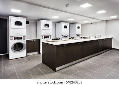 Powerful laundry machines and automatic dryers in big laundromat with a cupboard sinks for rinsing and tap water.