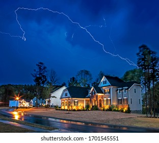 Powerful lightning storm front passes over residential houses, focus on the house, long exposure