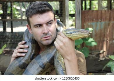 Powerful man struggling with gigantic anaconda