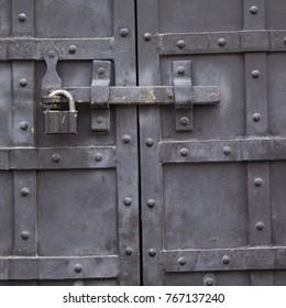 powerful metal door with rivets and padlock