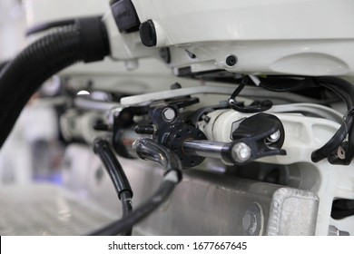 Powerful motor boat transom hydraulic steering of outboard engine close up - steering rod, cylinder, pipes and clamp