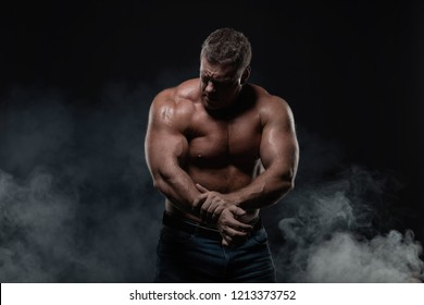 Powerful muscular bodybuilder posing on a black background. concept of strength and health