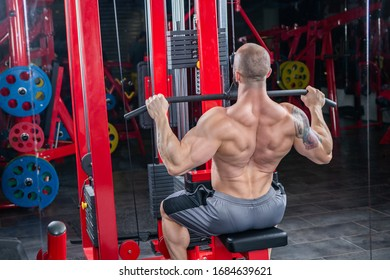 Powerful muscular man doing exercise for back on the lat machine