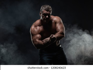powerful muscular man shows biceps on a black background. Strength and fitness concept