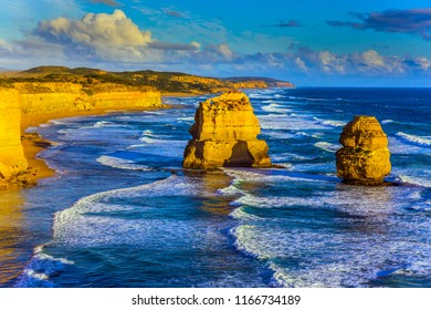 Powerful ocean surf and rocks of the Twelve Apostles at sunset. Grandiose coast of Australia. The concept of exotic, active and photo-tourism