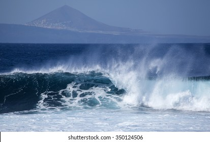 powerful ocean waves breaking by the shores of Gran Canaria, Graldar mountain in the background