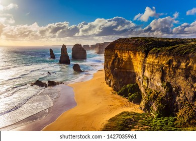 Powerful Pacific surf breaks down on the shore. Grandiose coast of Australia. Rocks of the Twelve Apostles at sunset. The concept of exotic, active and photo-tourism