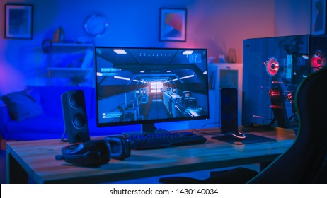 Powerful Personal Computer Gamer Rig with First-Person Shooter Game on Screen. Monitor Stands on the Table at Home. Cozy Room with Modern Design is Lit with Blue and Neon Light.
