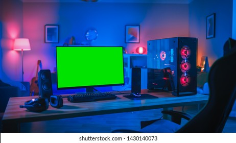 Powerful Personal Computer Gamer Rig with Mock Up Green Screen Monitor Stands on the Table at Home. Cozy Room with Modern Design is Lit with Pink Neon Light.