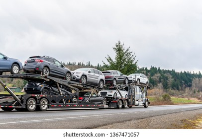 Powerful professional Big rig long haul car hauler semi truck transporting different cars on two levels modular semi trailer running on empty winding autumn road with trees on the hillside