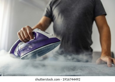 Powerful professional photo effect of water vapor from the hot iron. A modern lifestyle concept, a man who irons clothes at home
