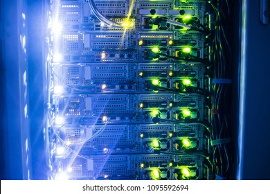 Powerful server hardware works in a dark server room. Technical hosting site of a large Internet provider.Modern high-speed Internet connection of network interfaces