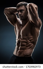 Powerful shirtless male bodybuilder posing over black background