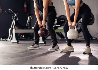 Powerful sportive people lifting up a heavy kettle ball in a gym, body building exercise. Body building workout in an indoor gym. Asian sportive people making a muscular and bodybuilding training. - Shutterstock ID 1878797569