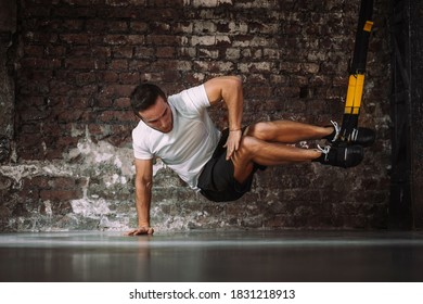 Powerful sportsman balancing on arm while doing exercise with TRX ropes against rough brick wall in gym