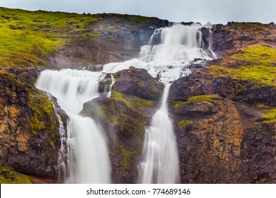 Powerful streams of cascade falls with a roar fall in a chasm. Cold and rainy July in Iceland. Concept of active and extreme tourism