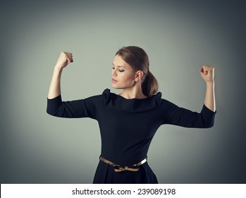 Powerful and strong business woman concept. Young female in dress looking at her muscled arms posing in studio.