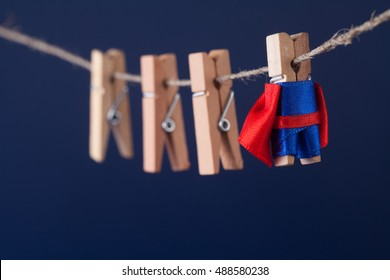 Powerful super hero conceptual photo with superstar clothespin character in blue suit red cape. leadership and wooden clothespins team at work. Dark blue background. soft focus. macro view