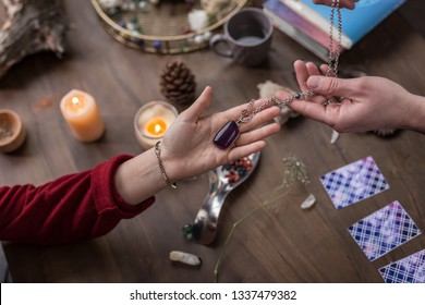Powerful talisman. Top view of a female hand above the table taking the necklace