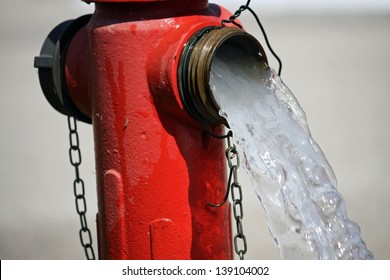 powerful water flow coming out with impetus from a street hydrant Red
