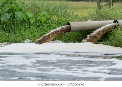 Powerful water flowing from a large pipe using a water pump for agricultural use in paddy fields.