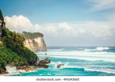 Powerful waves of Indian ocean hitting cliff in Bali, Indonesia. Sea nature landscape. Tropical nature of Bali, Indonesia. Beautiful sea waves and green tropics of Bali nature. Bali ocean waves