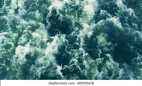 Powerful waves pulled out from fast moving boat, a huge stream of deep blue water with white foam rising up, steady beautiful shot, perfect for film, digital composition, Video Projection Mapping