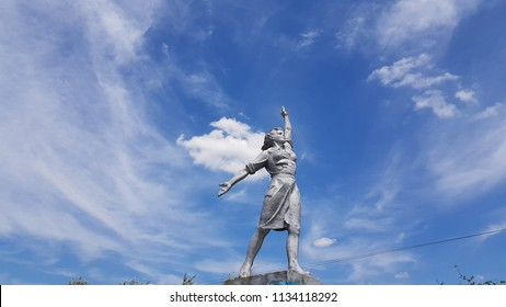 Powerful woman historical monument on blue sky with white clouds background. Social realism sculpture in Odessa countryside of Ukraine. Monumental Sculptures of Social-Realism. Soviet woman statue.