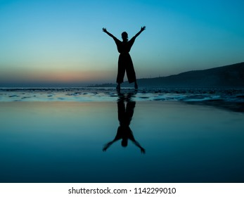powerful woman silhouette with wide trousers making Yes winner pose reflecting at the beachl during sunset in morocco with much space in the background