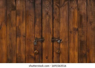 Powerful wooden doors with padlocks. Dark Wood texture