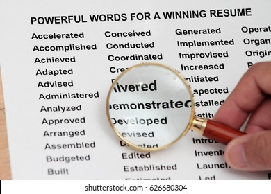 Powerful word for a winning  resume- magnifying glass searching for powerful word