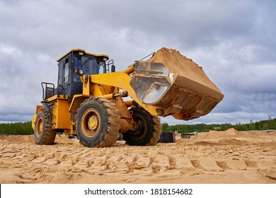 powerful yellow bulldozer crumbles sand at construction site