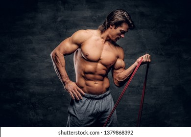 Powerful young bodybuilder is doing exercises with rubber. There is dark background.