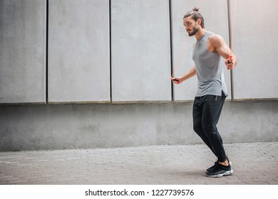 Powerful young man exercising outside. He does it at grey wall. Guy jumps and uses orange rope. He is concentrated on. Young man is alone.