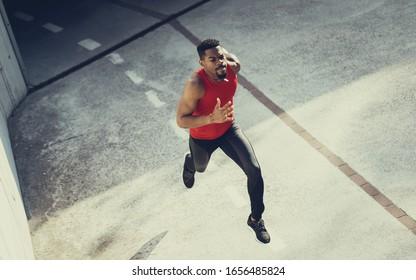 Kräftiger junger Mann, der sprintet. Fit motivierte schwarze Athleten laufen auf heißen Sommer in der Stadt.