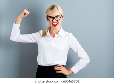 Powerful young woman on a gray background