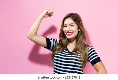 Powerful young woman on a pink background