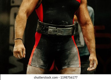 powerlifter in black suits and belt body in chalk magnesia