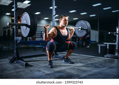 Powerlifter doing squats with barbell in gym